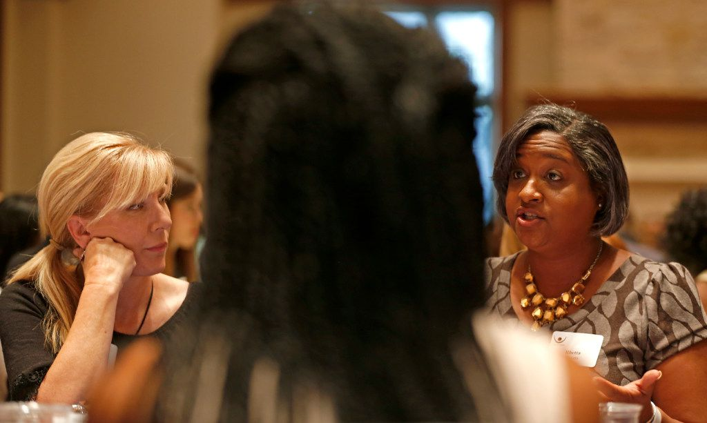 Rachel Ridge (left) listens to Rep. Rhetta Bowers, D-Dallas, at a dining table during the Together We Dine, a Dallas event created by Project Unity that aims at providing an open dialogue on race relations. Bowers, who is carrying the CROWN Act in the House, says a hearing on the bill is expected on April 29.