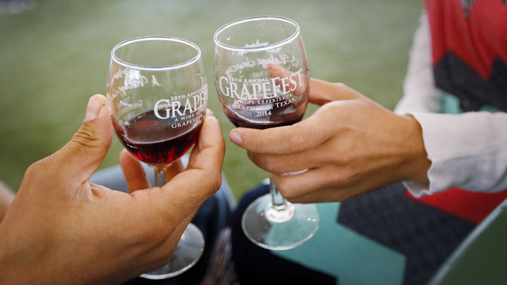 In this 2014 file photo, Wayne and his fiancee Diana Reese, from Houston, TX, toss their wine glasses during the Grapefest along Main Street in Grapevine, TX.