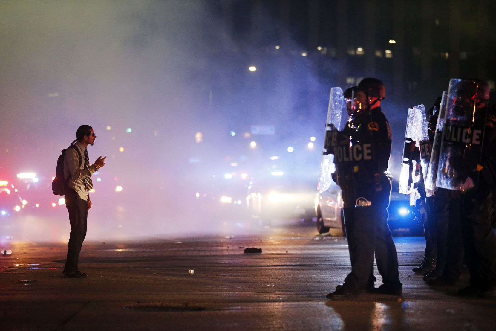 A protestor stands in the middle of the tear gas confronting tactical officers at the intersection of Young St. and S. Griffin St. in downtown Dallas, Friday, May 29, 2020. People were marching in protest of the in-custody death of George Floyd when they confronted Dallas Police tactical officers.