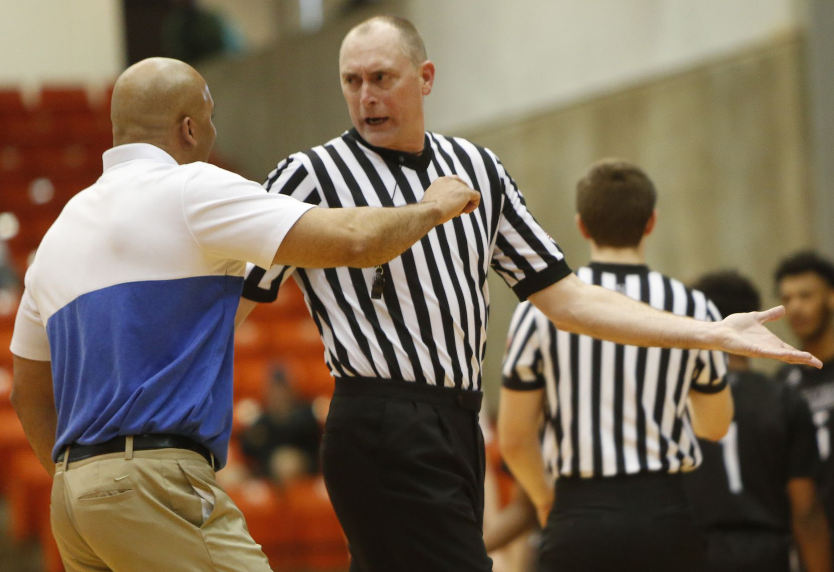 Duncanville head coach David Peavy converses with a game official during a second half timeout of their game against Odessa Permian. The two teams played in the Class 6A Region 1 championship boys basketball playoff game at Wilkerson-Greines Activity Center in Fort Worth on March 7, 2020.