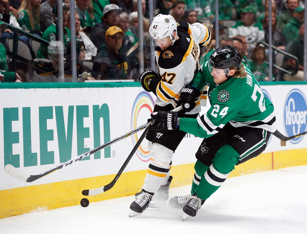 Boston Bruins defenseman Torey Krug (47) and Dallas Stars left wing Roope Hintz (24) go after the puck during the first period of play in the home opener at American Airlines Center in Dallas, Thursday, October 3, 2019. (Vernon Bryant/The Dallas Morning News)