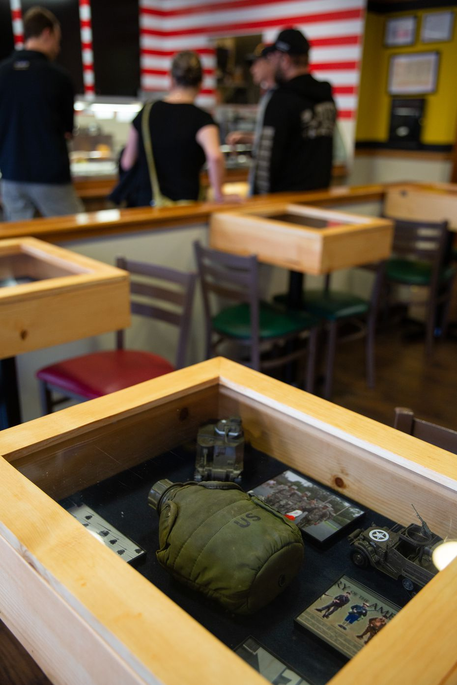 The tables serve as shadowboxes, showcasing military artifacts and memorabilia.