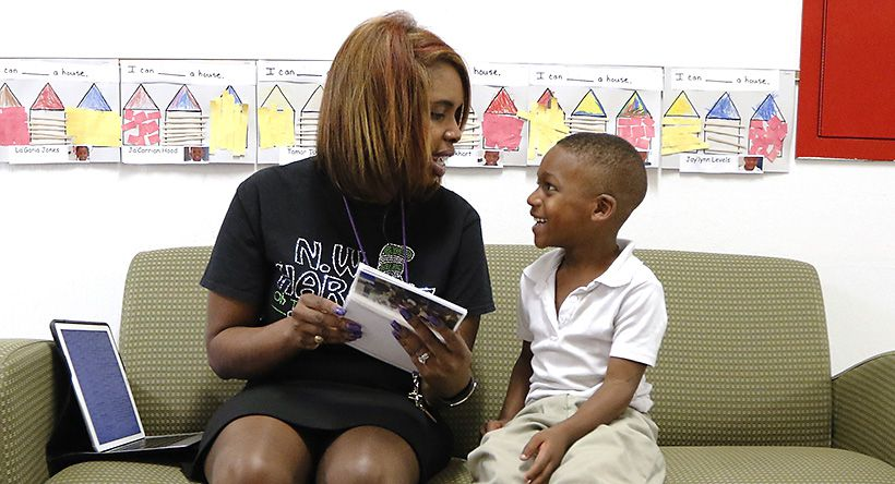 Principal Onjaleke Brown flips through a photo album with N.W. Harllee Early Childhood Center student A'lijah Pleasant, 5, on the love seat that serves as her mobile office in the school's hallways.