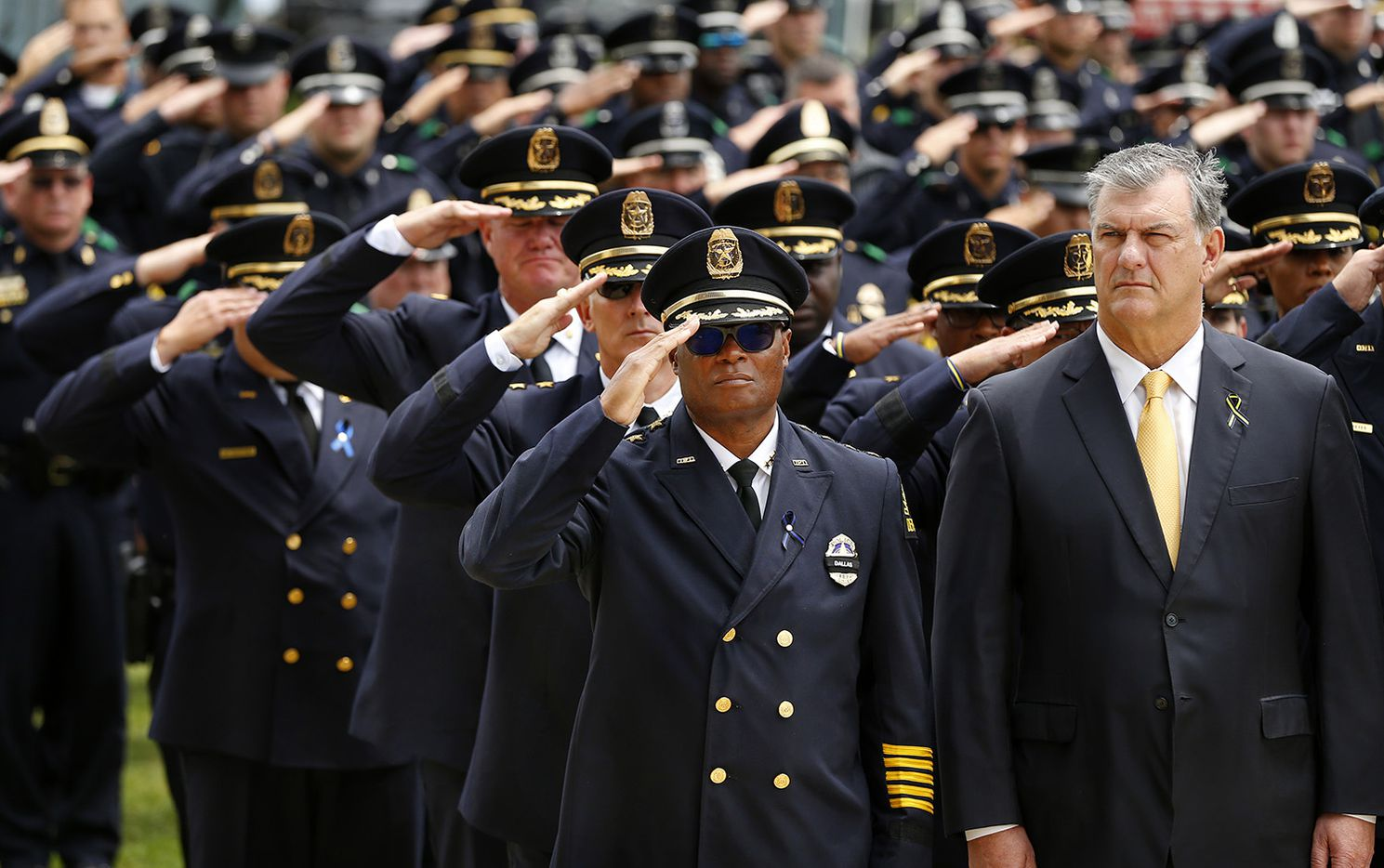 Dallas police Chief David Brown (center, left) salutes as Dallas Mayor Mike Rawlings (right) watches as the Color Guard carries slain Dallas police officer Michael Krol outside of Prestonwood Baptist Church in Plano, Texas, Friday, July 15, 2016. Krol was gunned down in an ambush attack in downtown Dallas a week ago. Four Dallas police officers and one DART officer were killed and several survived.