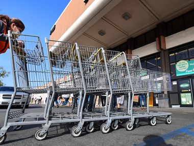 "A Food 4 Less employee pushed carts past workers gathered to protest in front of the supermarket in Long Beach, Calif., last week after a decision by owner Kroger to close two stores rather than pay workers an additional $4 an hour in ""hazard pay"" for their continued work during the coronavirus pandemic."