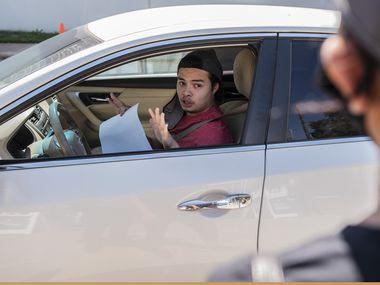 Mauricio Corrales, de 18 años, se registró en la fecha límite del 5 de octubre en el drive-thru organizado por el Departamento de Elecciones del Condado de Dallas.
