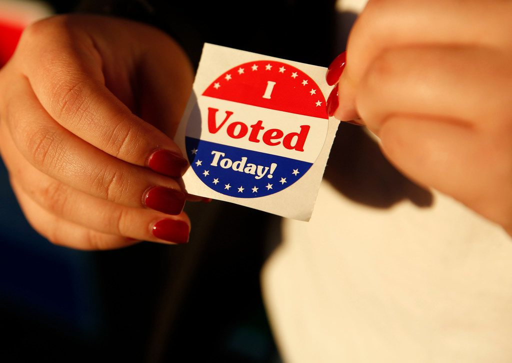 """Maria Garcia, a first-time voter, holds an """"I Voted Today!"""" sticker after casting her ballot during early voting at Samuell Grand Recreation Center in Dallas on Friday, Oct. 26, 2018."""