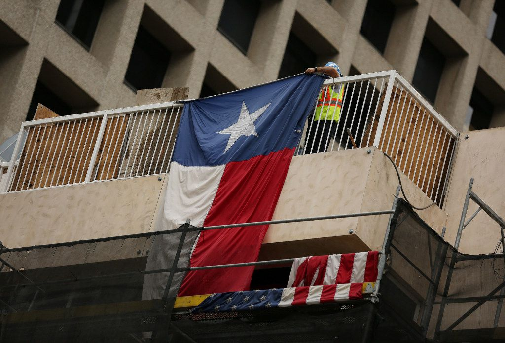 A construction worker repositions a Texas flag during development work in November at the northwest corner of Main Street and Field Street in downtown Dallas. (Andy Jacobsohn/The Dallas Morning News)