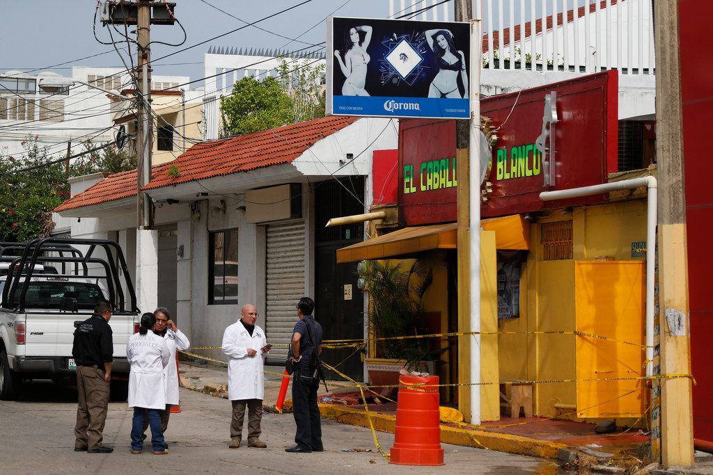 Investigators work outside the White Horse nightclub, the scene of the attack that killed more than two dozen staff and patrons, in Coatzacoalcos, Veracruz state, Mexico, Thursday, Aug. 29, 2019.