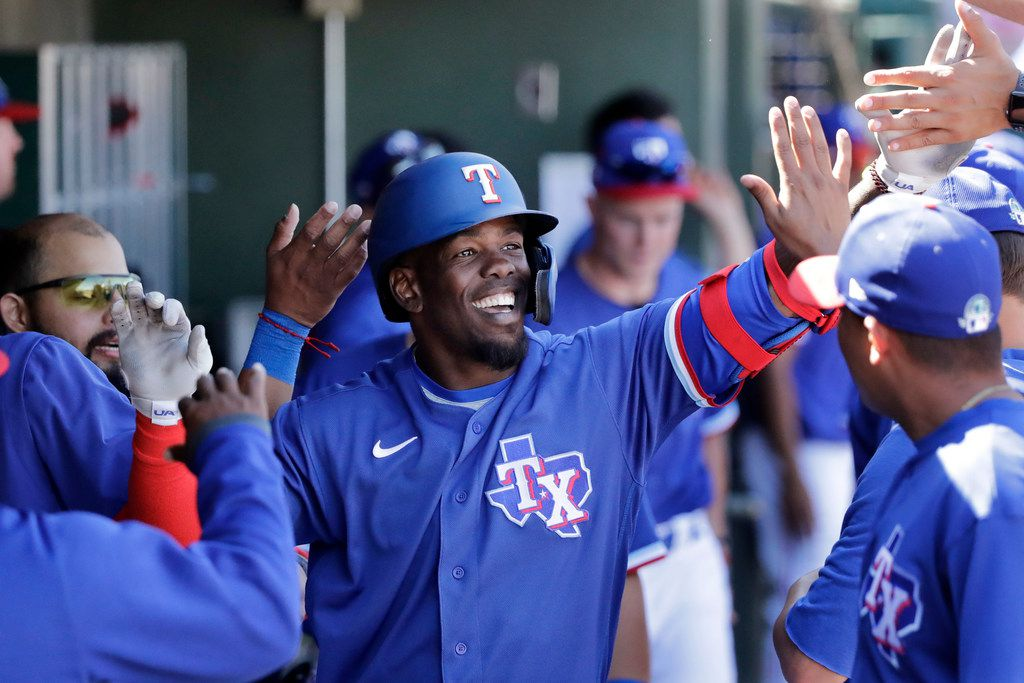Texas Rangers' Adolis Garcia is congratulated in the dugout after hitting a solo home run against the Arizona Diamondbacks in the third inning during a spring training baseball game Thursday, March 5, 2020, in Surprise, Ariz. (AP Photo/Elaine Thompson)