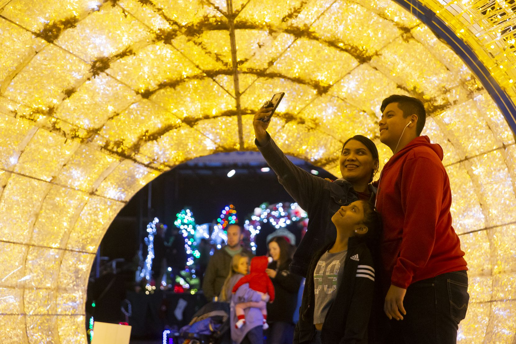 Liz Garcia takes a selfie with Gisselle Chuca, 10, and Jesus Chuca, 13, during Dallas Zoo Lights.