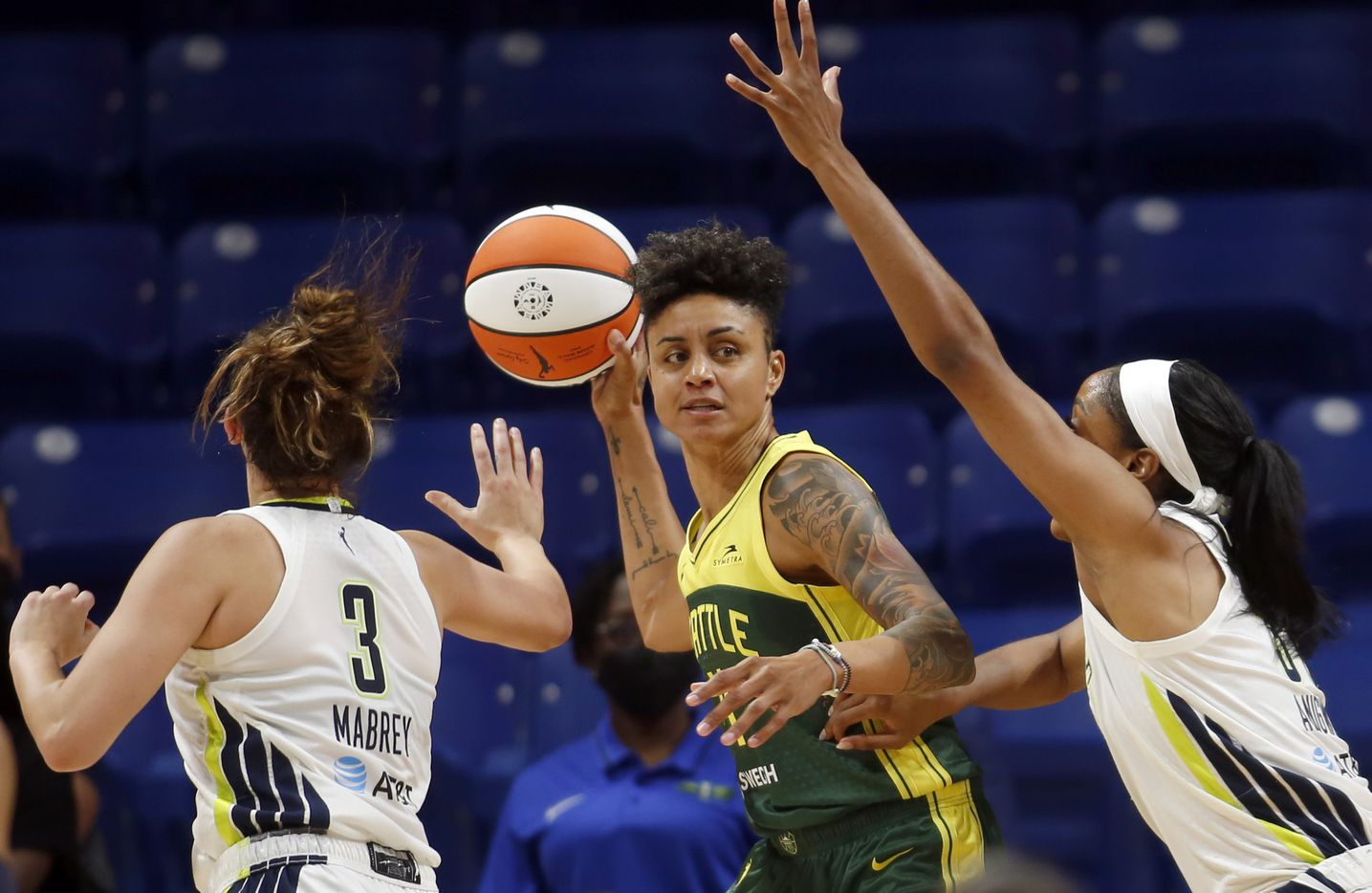 Seattle forward Candice Dupree (4) looks to pass as she faces the defense of Wings guard Marina Mabry (3), left, and center Kristine Anigwe (31) during second half action. The Wings hosted the Storm for their WNBA 2021season home opener at UTA's College Park Center in Arlington on May 22, 2021. (Steve Hamm/ Special Contributor)