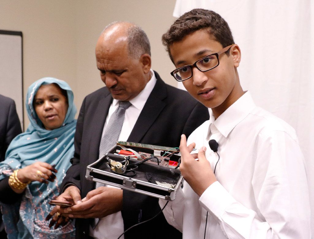 """Ahmed Mohamed, right, labeled """"Clock Boy"""" shows the clock he built in a school pencil box while standing with his parents, Muna Ibrahim, left, and Mohamed Elhassan, after a news conference in Dallas in August."""