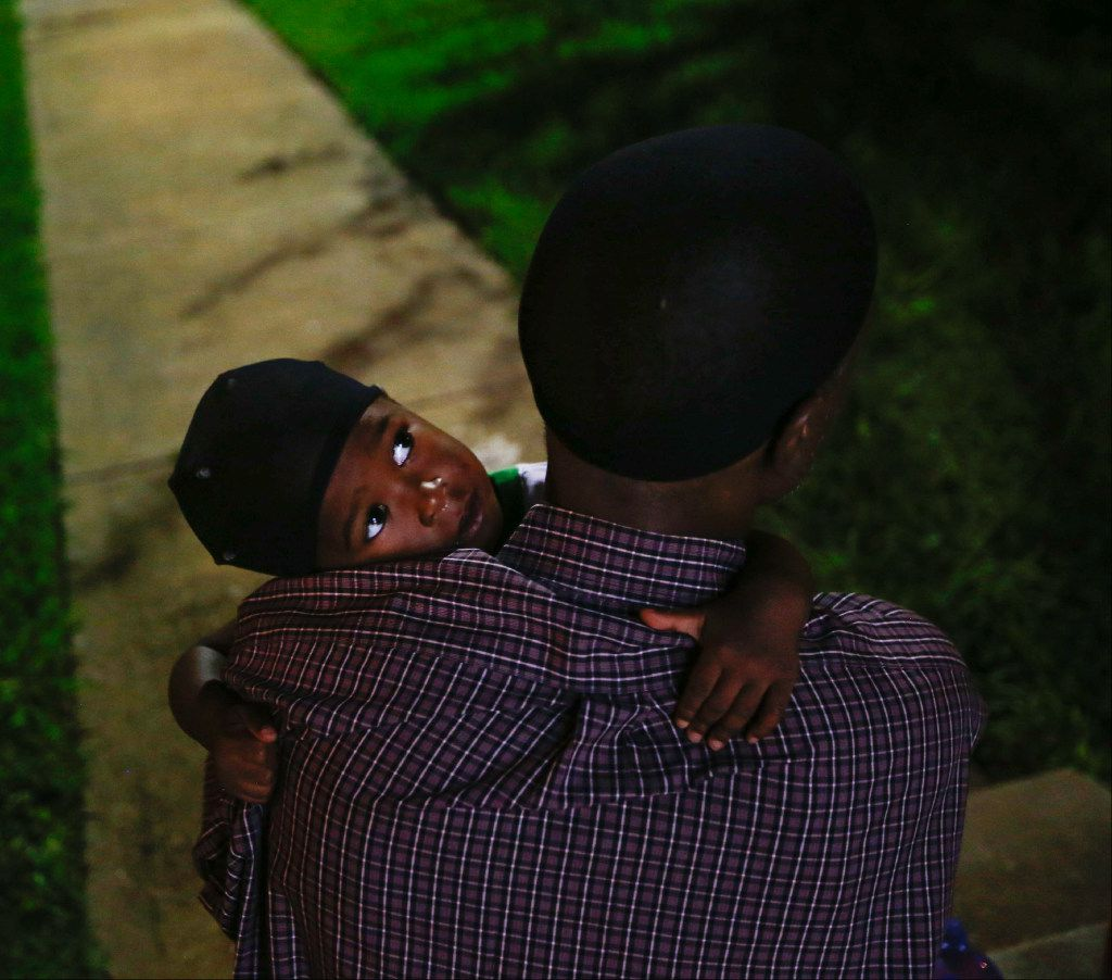 Jordan Miller, 2, sits on his fathers lap while they wait outside of The Family Place's men's shelter for a van to pick him up for his first day of day care. (Tailyr Irvine/The Dallas Morning News)