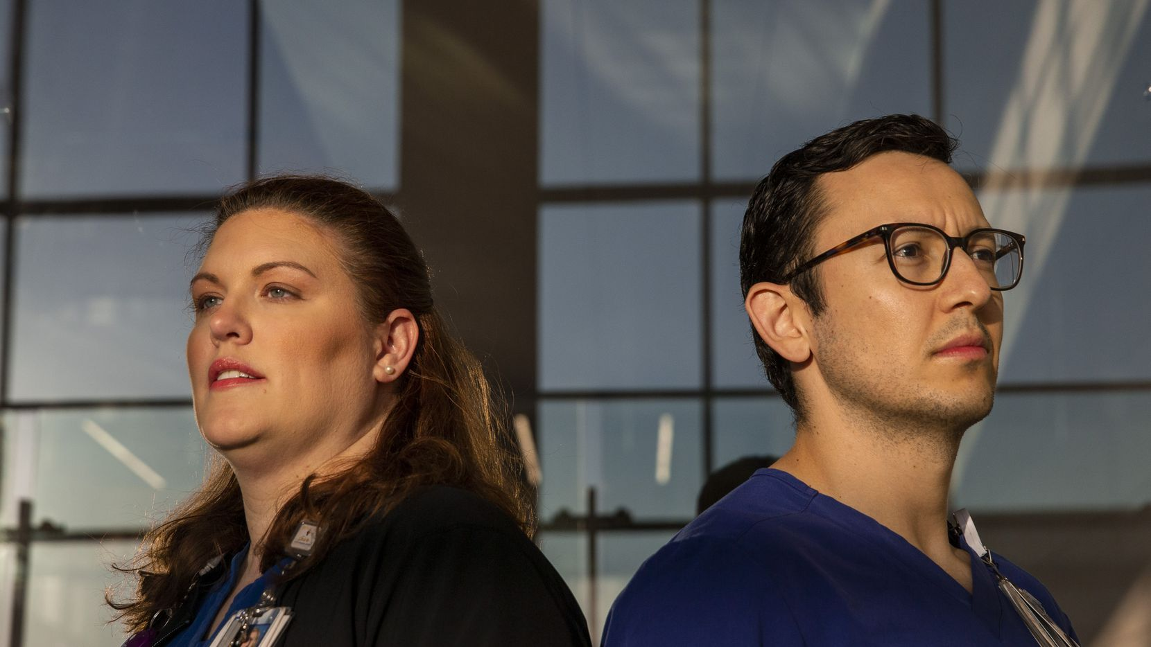"Registered nurses Megan Bennett and Otto Madrigal pose for a portrait outside Parkland Memorial Hospital in Dallas on Thursday after coming off their overnight shift. The two said a sense of optimism remains within their ICU. ""When patients first got here, it took us some extra steps in getting ready and the room ready for patients, but now we've got the process streamlined,"" said Bennett, who is associate manager of the unit."