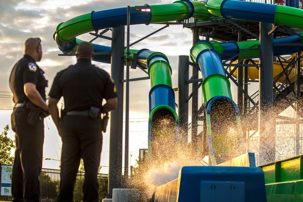 Officer A. Linwood, left, and Sgt. Jimmy Thomas, of the McKinney Police Department, watch kids ride a slide during a pool party in McKinney on Saturday.