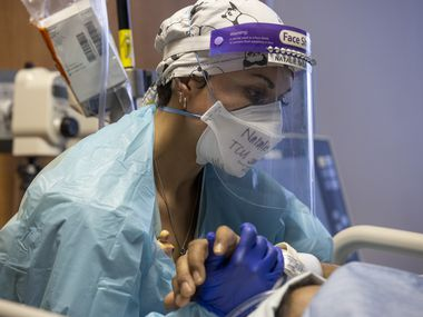 Nurse Natalie Salazar held the hand of an intubated COVID-19 patient in the Tactical Care Unit at Parkland Memorial Hospital as he received a chest tube placement to re-expand a punctured lung in February.