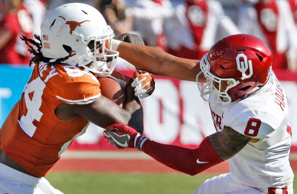 Texas Longhorns wide receiver Lil'Jordan Humphrey (84) is grabbed by Oklahoma Sooners safety Kahlil Haughton (8)  after a pass catch during the Oklahoma University Sooners vs. the University of Texas Longhorns NCAA college football game at the Cotton Bowl in Dallas on Saturday, October 14, 2017. (Louis DeLuca/The Dallas Morning News)