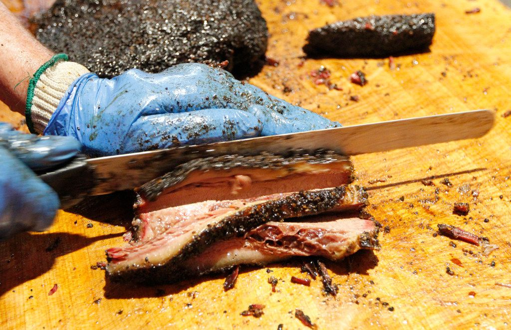 In this pre-pandemic photo, a worker at Cattleack Barbecue in Farmers Branch slices smoked brisket. Coronavirus has driven up beef prices and threatened some barbecue businesses.