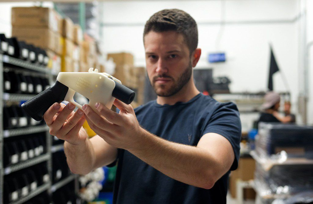 "Cody Wilson, owner of Defense Distributed company, holds a 3D printed gun, called the ""Liberator"", in his factory in Austin, Texas on August 1, 2018. A US gun rights advocate began gearing up for a legal fight Wednesday to be able to publish online blueprints for 3D-printed firearms, as the White House signaled support for a federal judge's decision to block the venture. Cody Wilson's Texas-based company Defense Distributed had briefly made the blueprints available online, but Seattle-based US District Judge Robert Lasnik granted an injunction Tuesday to take the material down."