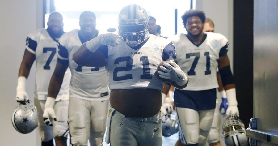 """Dallas Cowboys offensive guard Joe Looney (73) makes his way to the field in a Dallas Cowboys running back Ezekiel Elliott (21) jersey and gesturing the """"feed me,"""" motion as more of the offensive line laugh behind him prior to practice during training camp at The Star in Frisco on Tuesday, August 22, 2017."""