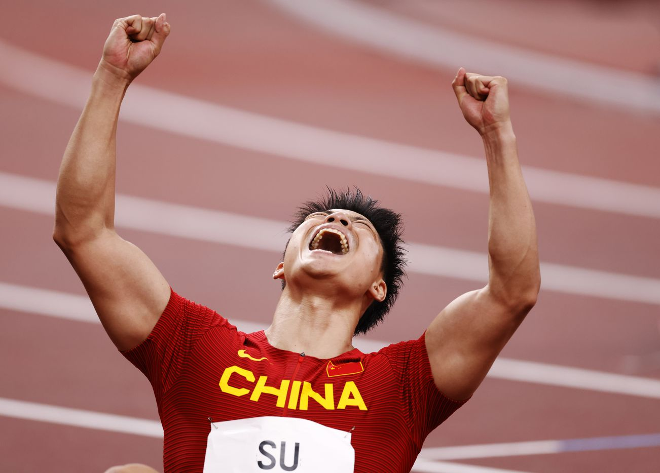 China's Su Bingtian celebrates his run in the 100 meter semifinal during the postponed 2020 Tokyo Olympics at Olympic Stadium, on Sunday, August 1, 2021, in Tokyo, Japan. Bingtian ran a 9.83 and advanced to the final.  (Vernon Bryant/The Dallas Morning News)