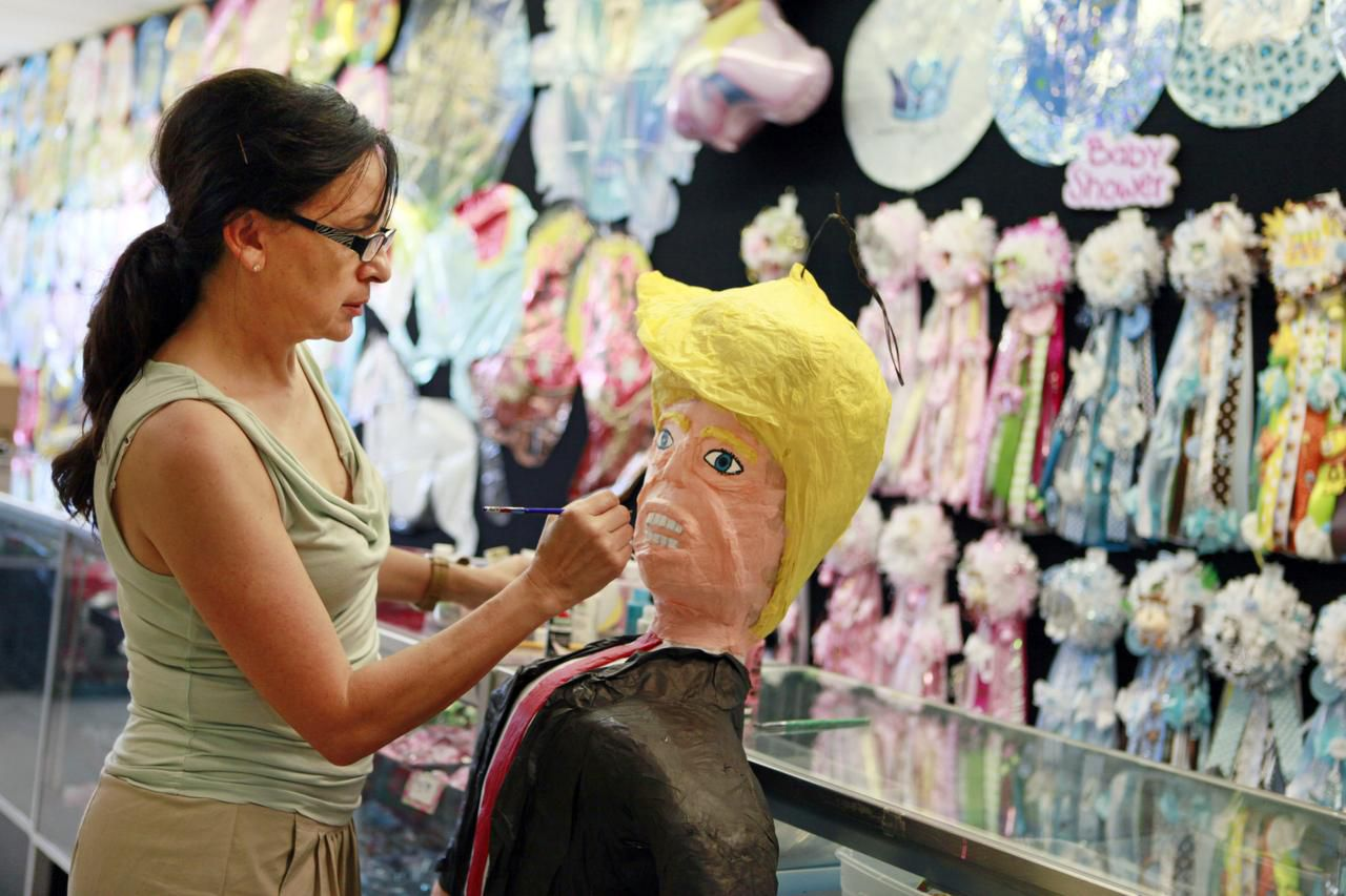 Co-owner Elvie de la Fuente of ABC Party Headquarters on West Davis Street in north Oak Cliff decorates a Donald Trump piñata at her family's business. The shop sold its first one this week for $65.