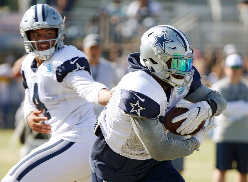 Dallas Cowboys quarterback Dak Prescott (4) hands the ball off to Dallas Cowboys running back Ezekiel Elliott (21) on a run play during the afternoon practice at training camp in Oxnard, California on Monday, July 31, 2017. (Vernon Bryant/The Dallas Morning News)