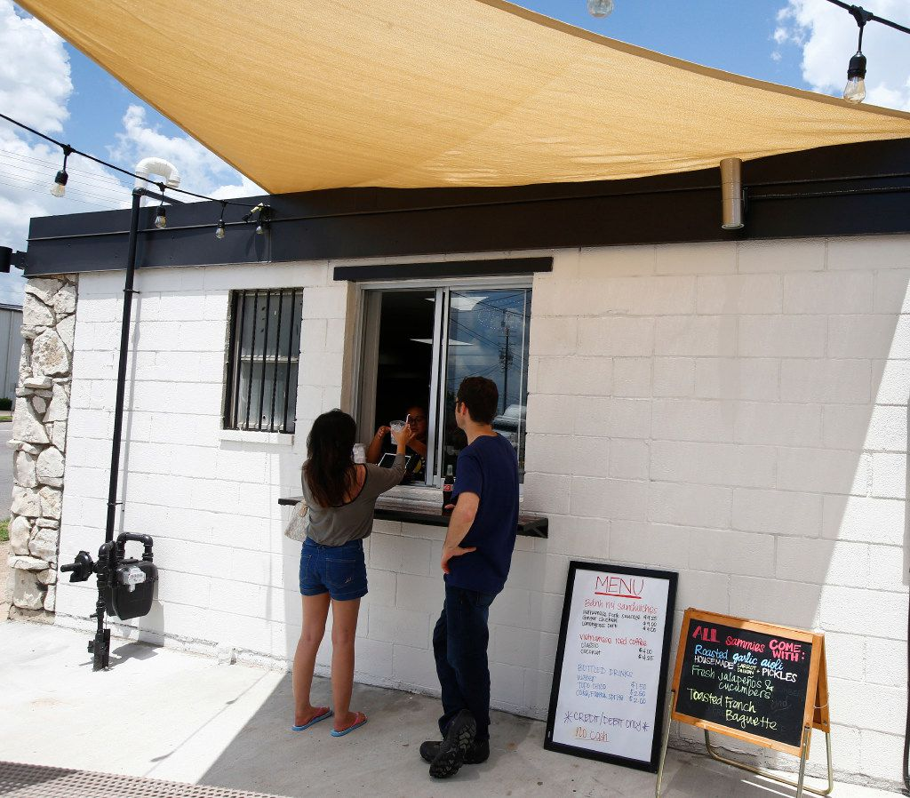 Mai La (left) and Jonathan Cheatham get their drinks from the service window at Sandwich Hag in Dallas on July 7, 2017.  (Nathan Hunsinger/The Dallas Morning News)