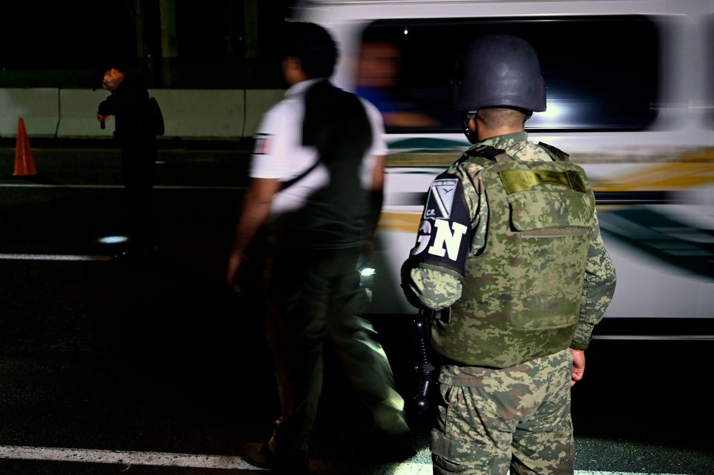 Miembros de la Guardia Nacional de México esperan a un grupo de migrantes en un punto de revisión cerca de Tapachula, Chiapas.