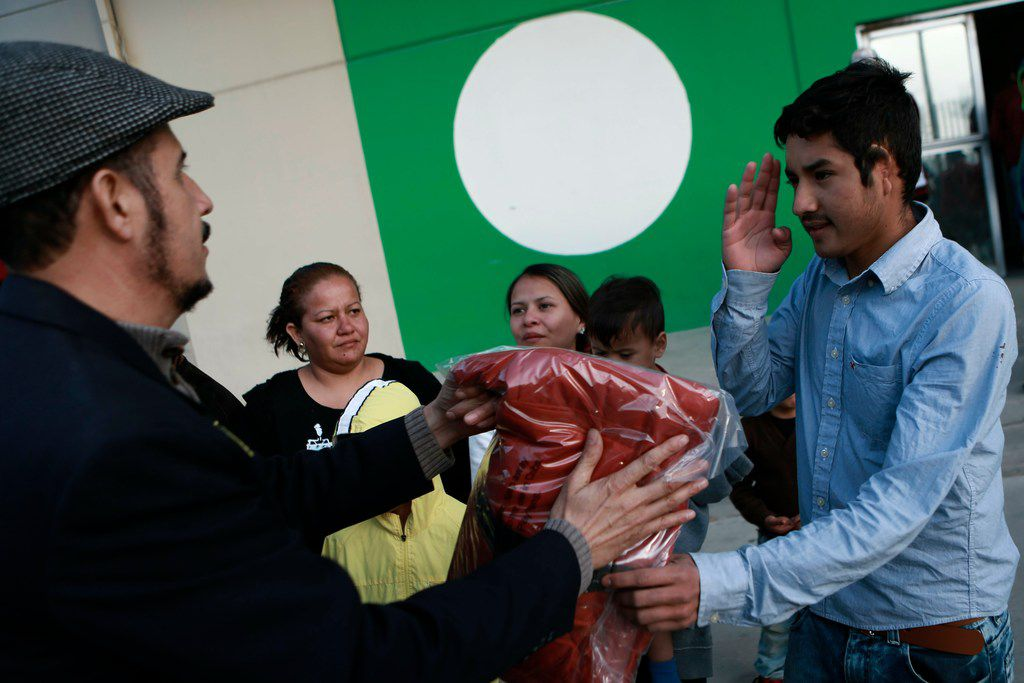 A migrant, right, thanks a resident gifting plastic coats to migrants who are living at a shelter set up inside Bachilleres gymnasium in Ciudad Juarez, Mexico, Tuesday, Feb. 19, 2019.