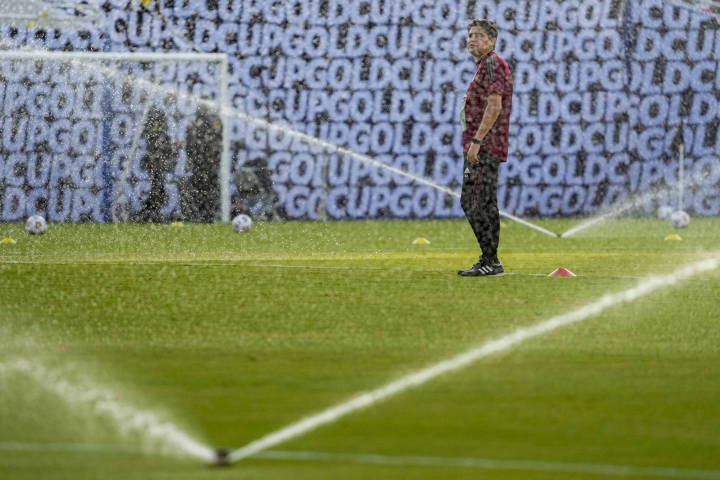 Mexico staff prepare for warmups as water sprays on the field before a CONCACAF Gold Cup Group A soccer match against Guatemala at the Cotton Bowl on Wednesday, July 14, 2021, in Dallas.
