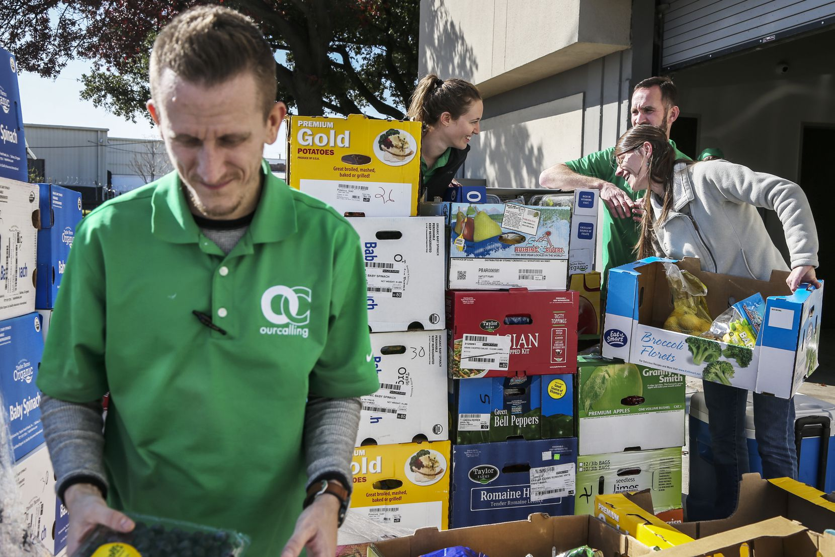 Joshua Brown, (left) operations technician, sorts through donated produce with other staff members at Our Calling in Dallas on Dec. 10, 2018.