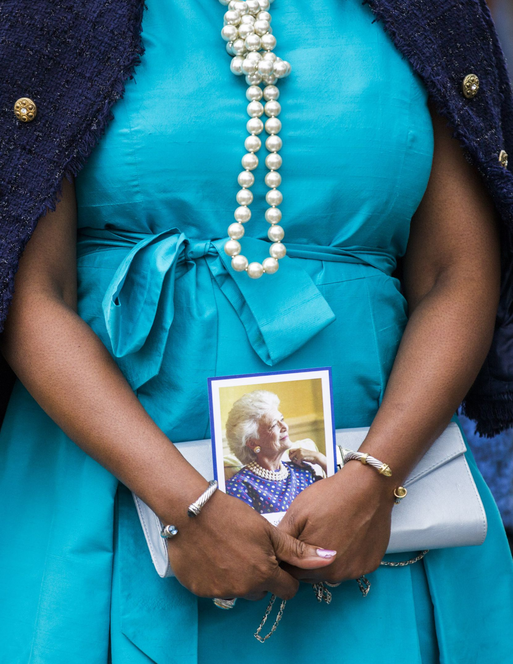 A woman wears pearls and carries a photo of Barbara Bush as she and other guests leave after viewing the casket of former First Lady Barbara Bush on April 20, 2018 at St. Martin's Episcopal Church in Houston.