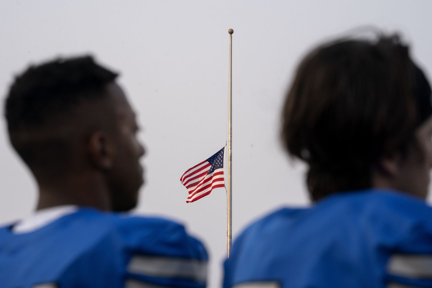 The American flag flies at half staff to commemorate the 20th anniversary of the 9/11 terrorist attacks as Plano West players stand for the national anthem before a high school football game against Little Elm on Friday, Sept. 10, 2021 at John Clark Stadium in Plano, Texas. (Jeffrey McWhorter/Special Contributor)