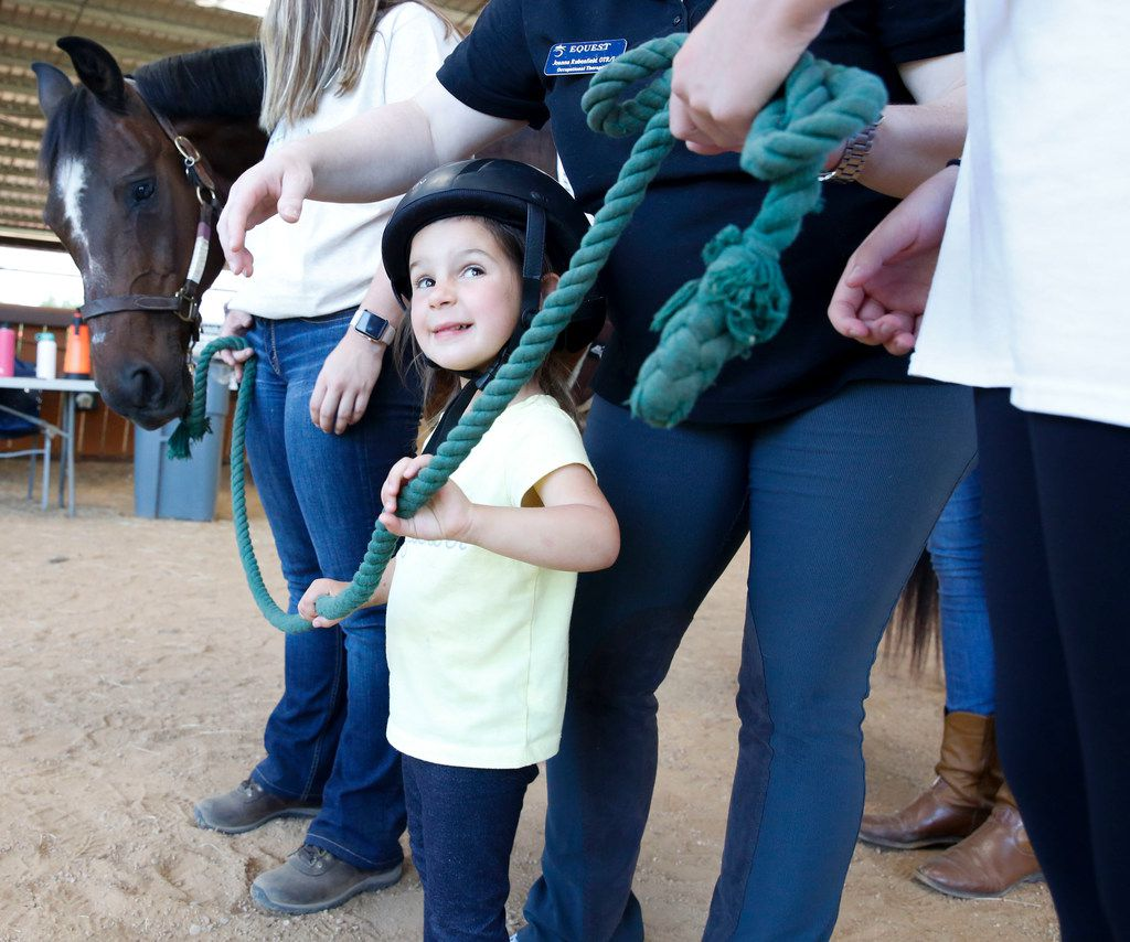 Three-year-old Mora Wolf holds onto her horse's reins as she prepares to lead Hombre back to the barn after an occupational therapy session at Equest at the Texas Horse Park in Dallas on Wednesday.