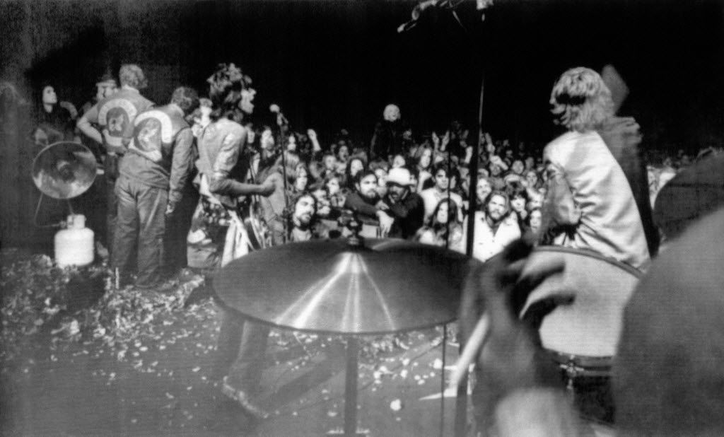 Rolling Stones Keith Richards (left) and Mick Jagger (right) sing on the rose petal-littered stage during the  concert at Altamont Speedway on  Dec. 6, 1969. Hells Angels (far left) held back the surging crowd. The hand of drummer Charlie Watts is shown in foreground.