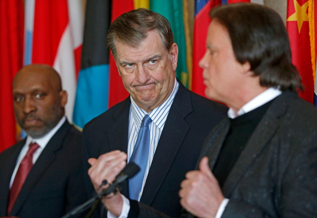 Dallas Mayor Mike Rawlings, center, looks at David R. Carey, right, Executive Vice President of T-Mobile, next to City Manager T.C. Broadnax during a press conference about the 911 issue with T-Mobile at Dallas City Hall on Wednesday, March 15, 2017, in Dallas. (Jae S. Lee/The Dallas Morning News via AP)