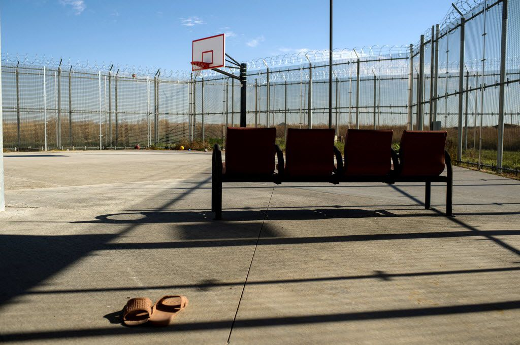 A forgotten pair of slippers sit on the basketball court behind barbed wire fence at the Kiyuksa O'Tipi Reintegration Center in Kyle, a juvenile detention center, on Pine Ridge Reservation in South Dakota, on Oct. 20, 2014. Dr. Stanley Patrick Weber, later convicted of molesting children, worked on this reservation among others.