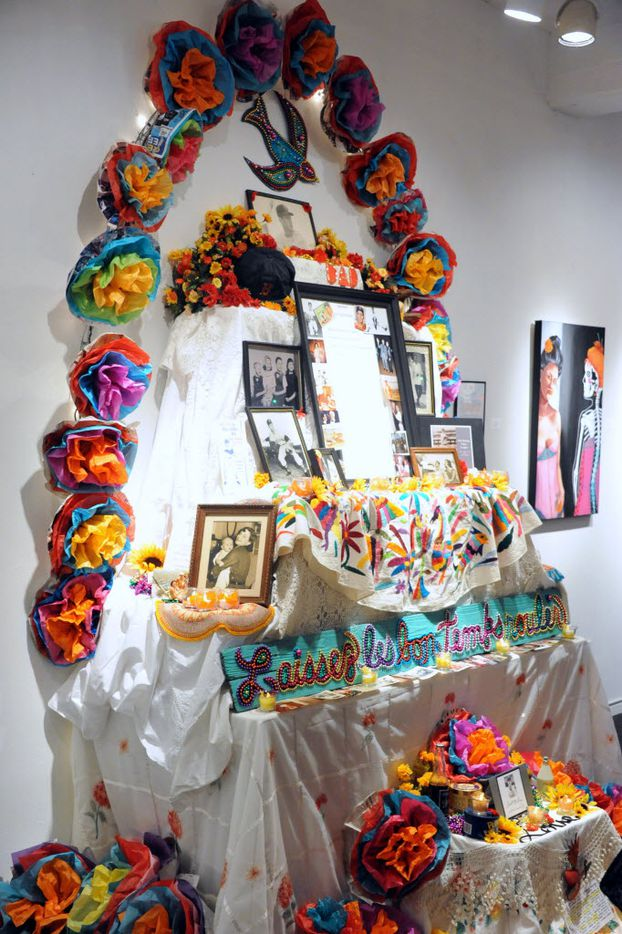 A Dia de los Muertos shrine displays photographs, baseball hats and colorful flowers at the 27th annual Dia de los Muertos Art Exhibition at Dallas' Bath House Cultural Center in 2013.