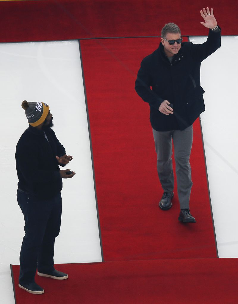 Troy Aikman, right, joins Ricky Williams, left, on the ice to participate in the puck drop prior to a NHL Winter Classic matchup between the Dallas Stars and the Nashville Predators on Wednesday, January 1, 2020 at Cotton Bowl Stadium in Dallas. (Ryan Michalesko/The Dallas Morning News)