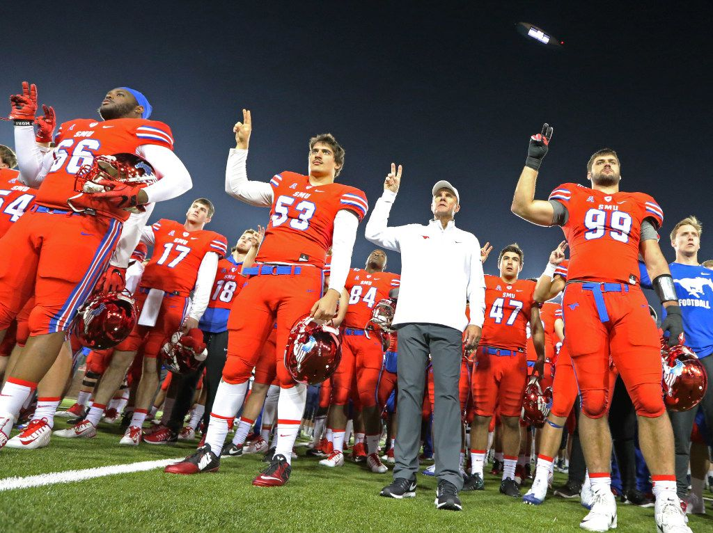 SMU head coach Chad Morris stands with his players as the school song is played following SMU's 75-31 loss during the Navy Midshipmen vs. the SMU Mustangs NCAA football game at Ford Stadium in Dallas on Saturday, November 26, 2016. (Louis DeLuca/The Dallas Morning News)