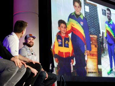 NASCAR Cup driver Ricky Stenhouse, Jr. (right) laughs at his social media post projected  during Media Day at Texas Motor Speedway in Fort Worth, Wednesday, February 26, 2020. The image shows him as a young kid (and adult) decked out in former driver Jeff Gordon's racing colors. The emcee attempted to embarrass each driver with one of their posts. (Tom Fox/The Dallas Morning News)