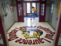 Custodian Debra Booty disinfects high touch areas in a hallway at Paul L. Dunbar Learning Center on Thursday, July 30, 2020, in Dallas. (Smiley N. Pool/The Dallas Morning News)