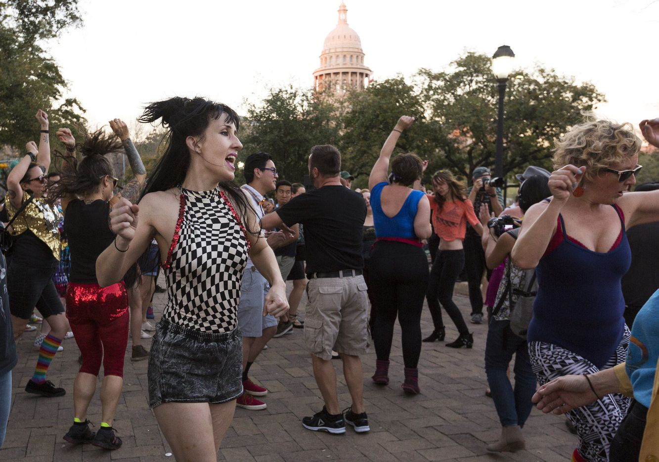 Adrienne Anemone, left, dances at a party to show support of the LGBTQ community gathered in front of the Governor's Mansion in Austin on Thursday, Feb. 23, 2017.