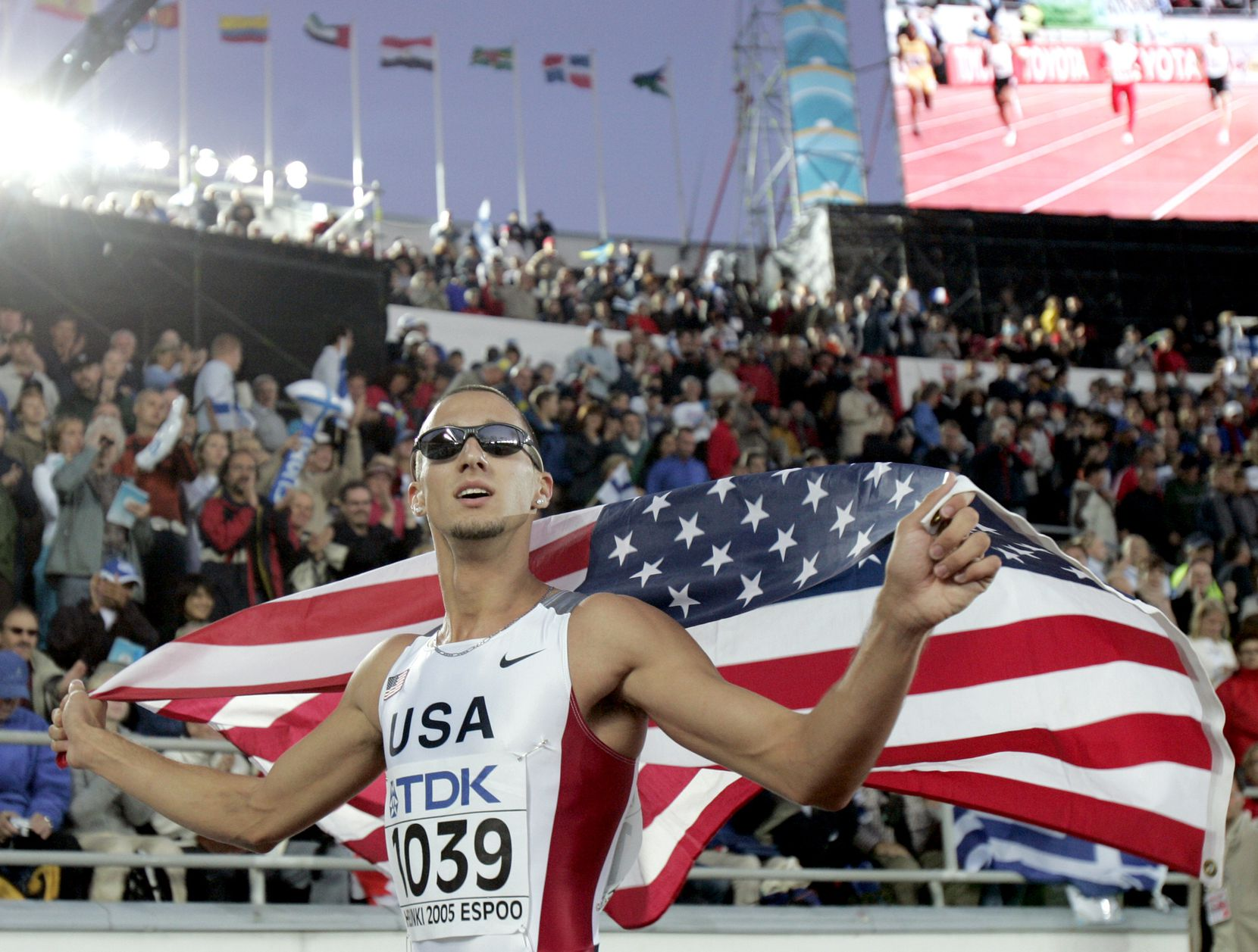eremy Wariner of the US poses with the Stars and Stripes after winning the gold medal in the final of the Men's 400 meters at the World Athletics Championships in Helsinki, Finland, Friday, Aug. 12, 2005.