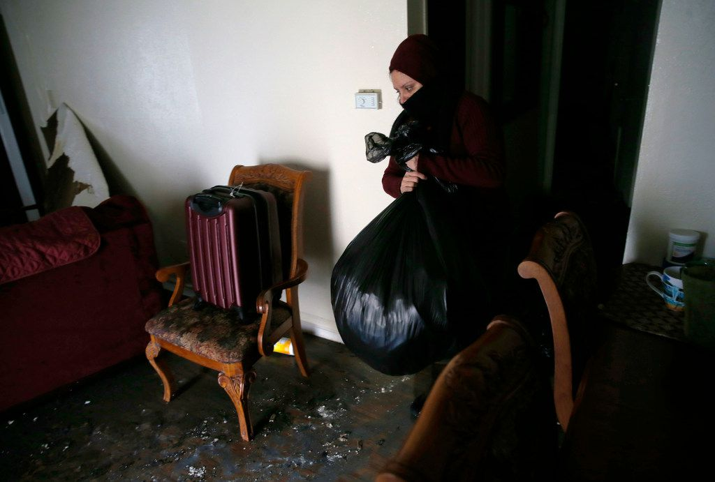 Yamilet Romero removes salvageable items from her apartment after a fire damaged eight units at Del Rey Village Apartments in Dallas on Friday, March  1, 2019.