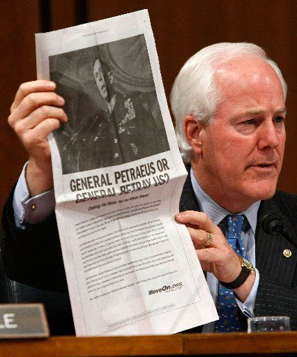 In this 2007 file photo, Sen. John Cornyn, R-Texas, holds up a copy of an ad paid for by MoveOn.org during a hearing of the Senate Armed Services Committee with Gen. David Petraeus.