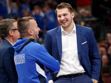 Dallas Mavericks forward Luka Doncic (right) laughs along with Dallas Mavericks guard J.J. Barea (center) during a second half timeout against the Boston Celtics at the American Airlines Center in Dallas, Wednesday, December 18, 2019.