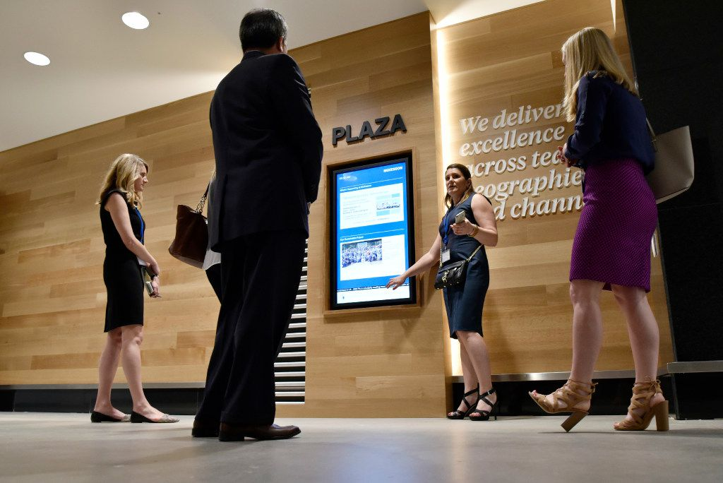 Sara Baldi (center), McKesson's vice president of global workplace, describes interactive multimedia signage located on every floor of the health care giant's new offices in Irving.